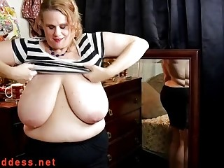 Trying on tight clothes over her massive tits